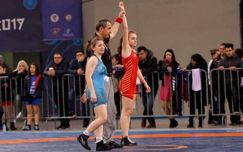 Dos luchadoras junto a un árbitro en la Acrópolis Cup