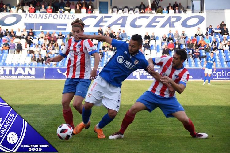 El futbolista del Linares Pedro Beda en una disputa con dos rivales del Poli Almería.