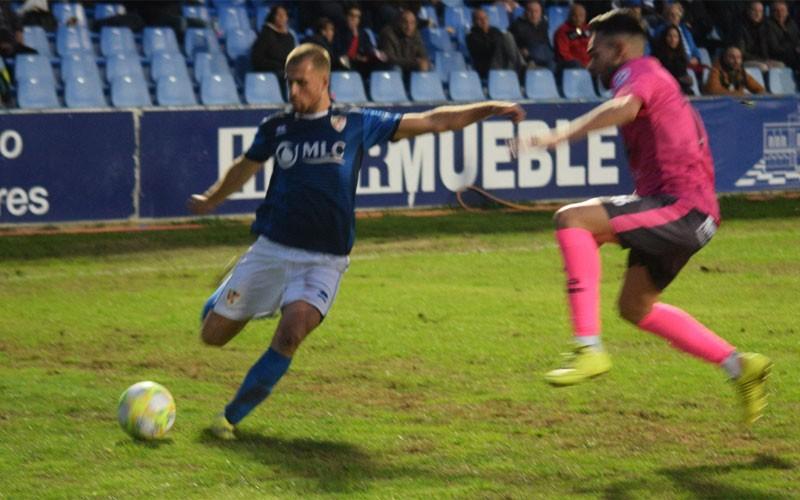 Un jugador del Linares centrando un balón ante la presión de un futbolista del antequera